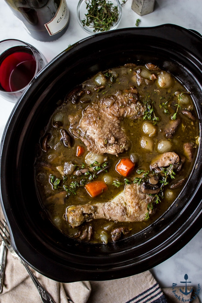 Overhead photo of Slow Cooker Coq Au Vin in a black slow cooker with a bottle of wine , glass of wine and salt and pepper shakers in background.