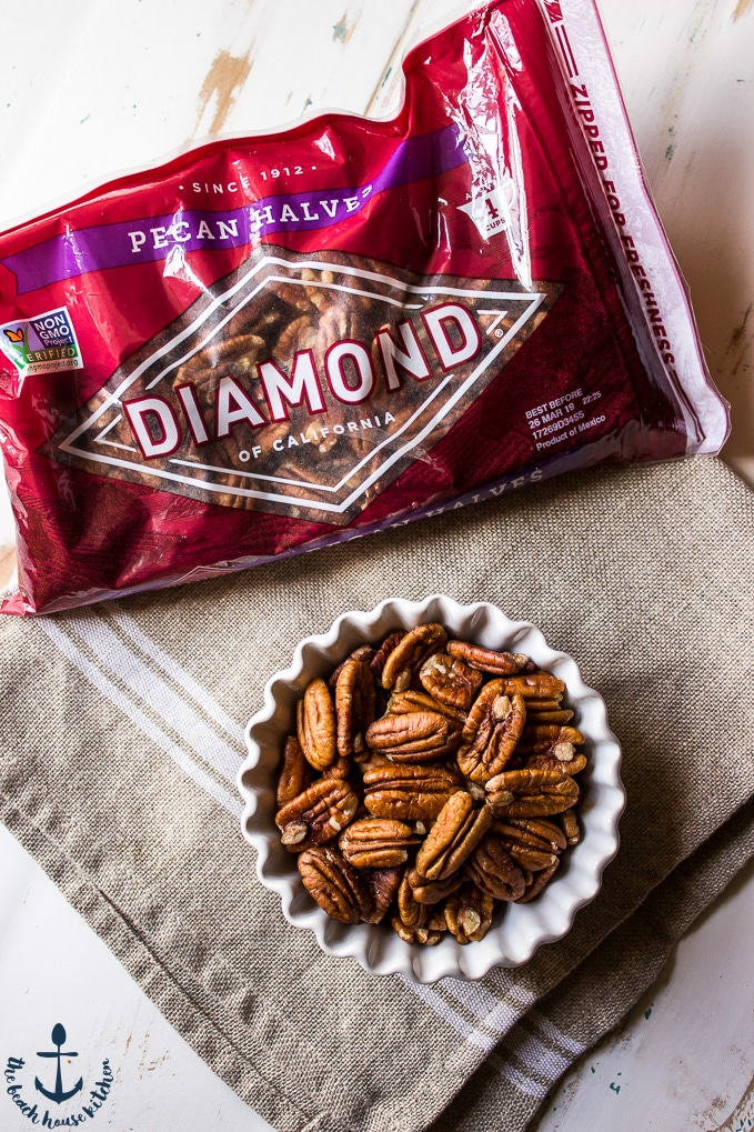 Pecans in a white bowl with a bag of Diamond pecans