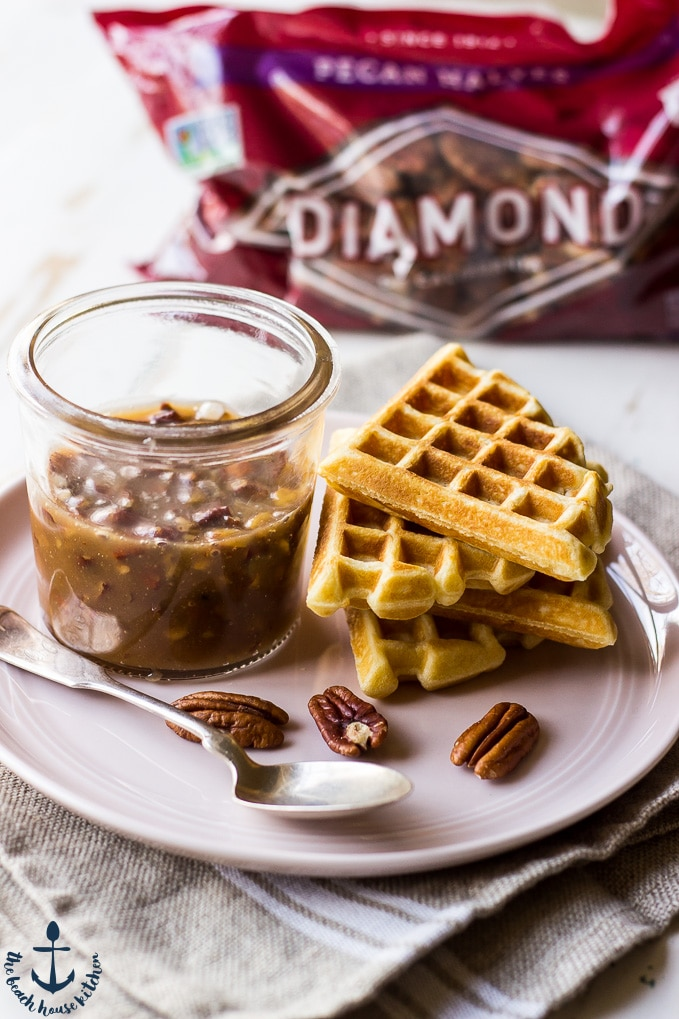 Easy Pecan Waffles with Pecan Praline Sauce on a pink plate with a bag of Diamond pecans in the back ground