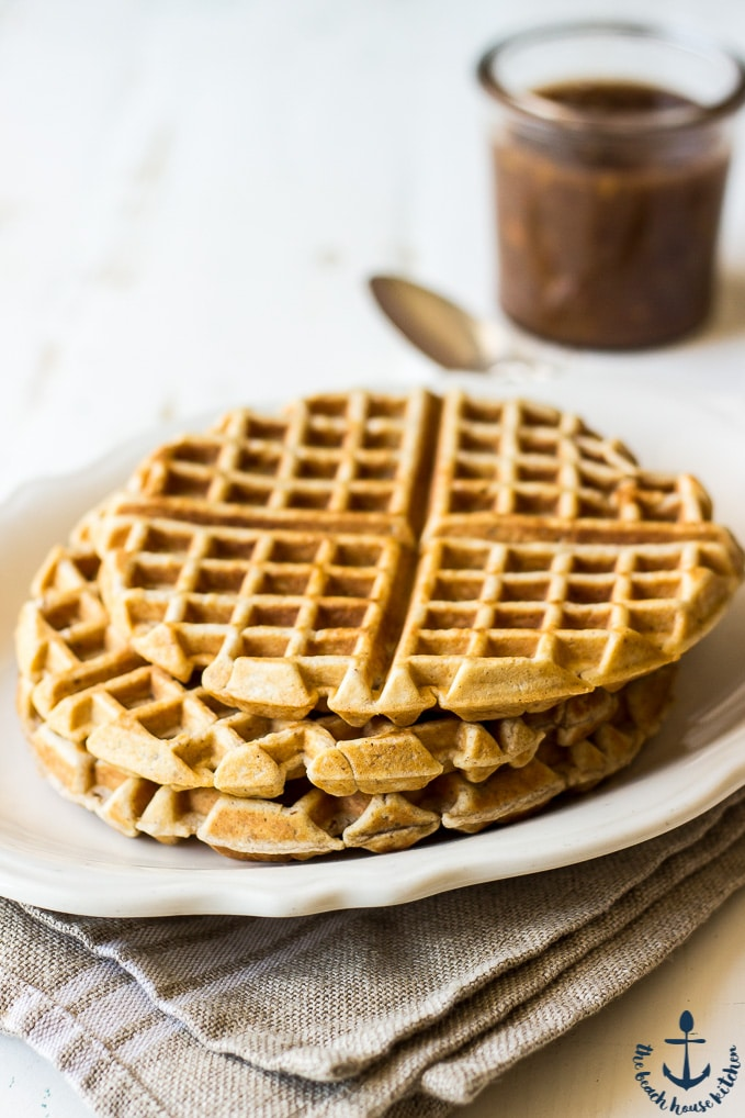 A white plate with a stack of pecan waffles