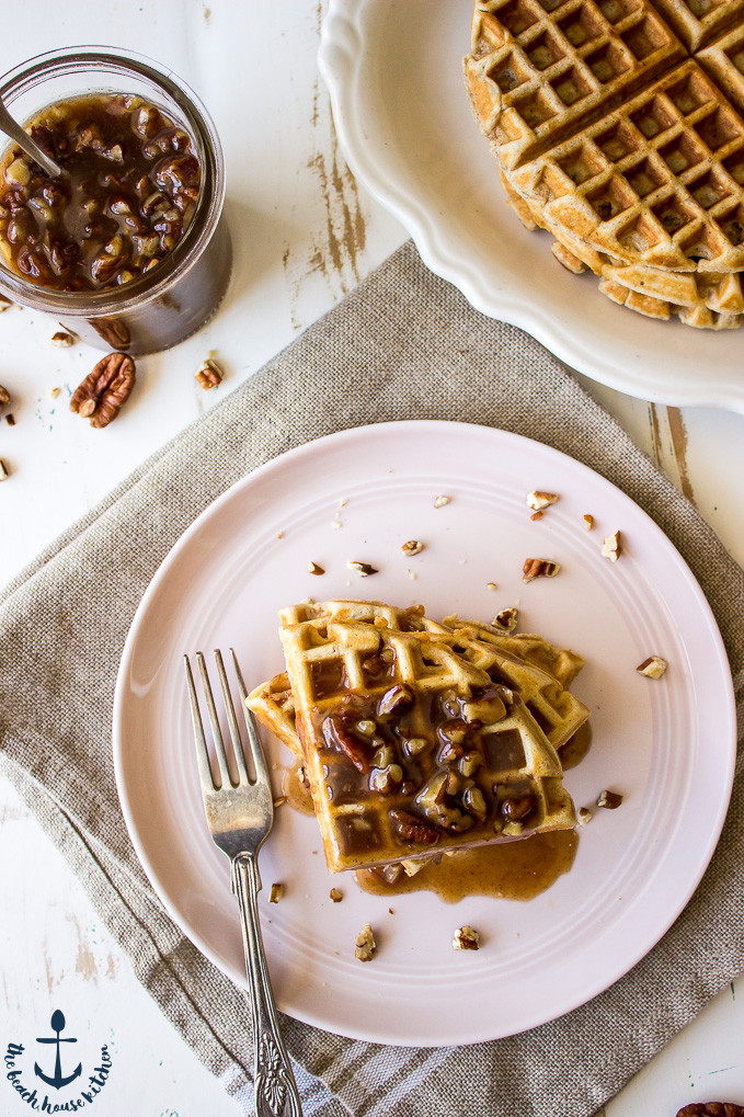 Overhead photo of Easy Pecan Waffles on a pink plate with a jar of with Pecan Praline Sauce and a white plate of plain waffles