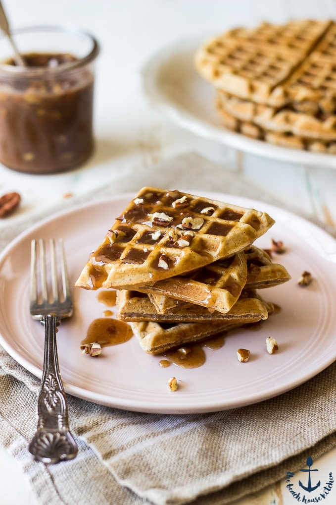 Easy Pecan Waffles with Pecan Praline Sauce on a pink plate with a silver fork
