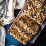 Overhead shot of loaded muesli quick bread on white rectangular plate with silver measuring spoons.