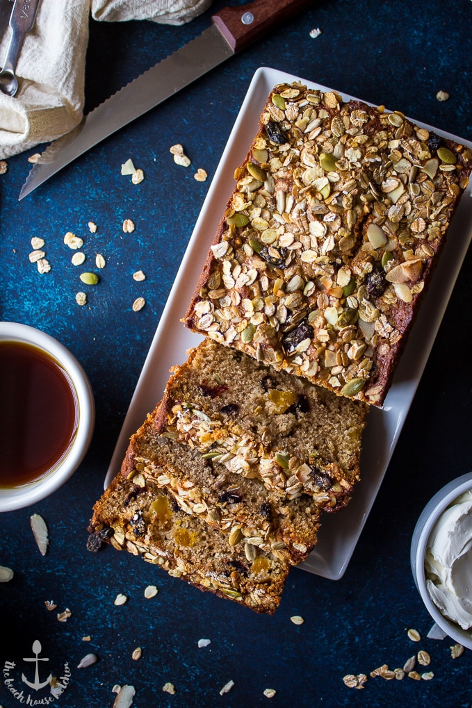 Overhead shot of loaded muesli quick bread on white rectangular plate with cup of coffee and sharp knife.