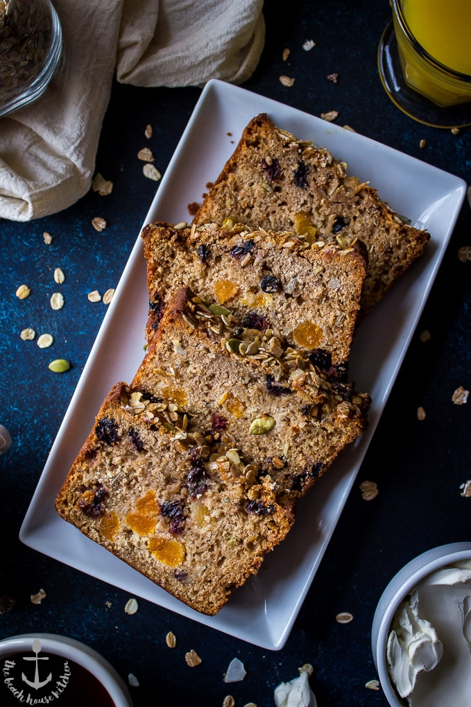 Overhead shot of four slices of loaded muesli quick bread on white rectangular plate.
