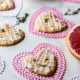 Pink Grapefruit and Thyme Shortbread Hearts on heart doilies with thyme leaves and pink grapefruit in background.
