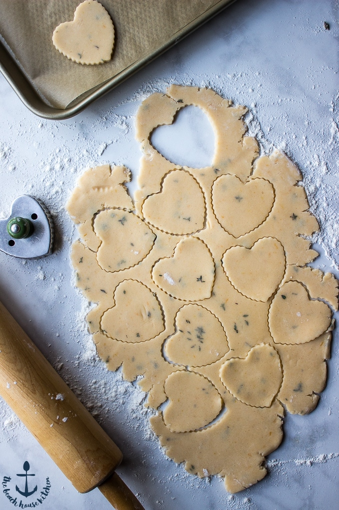Overhead shot of hearts cutouts with cookie dough. Rolling pin, cookie cutter, and tray in photo.