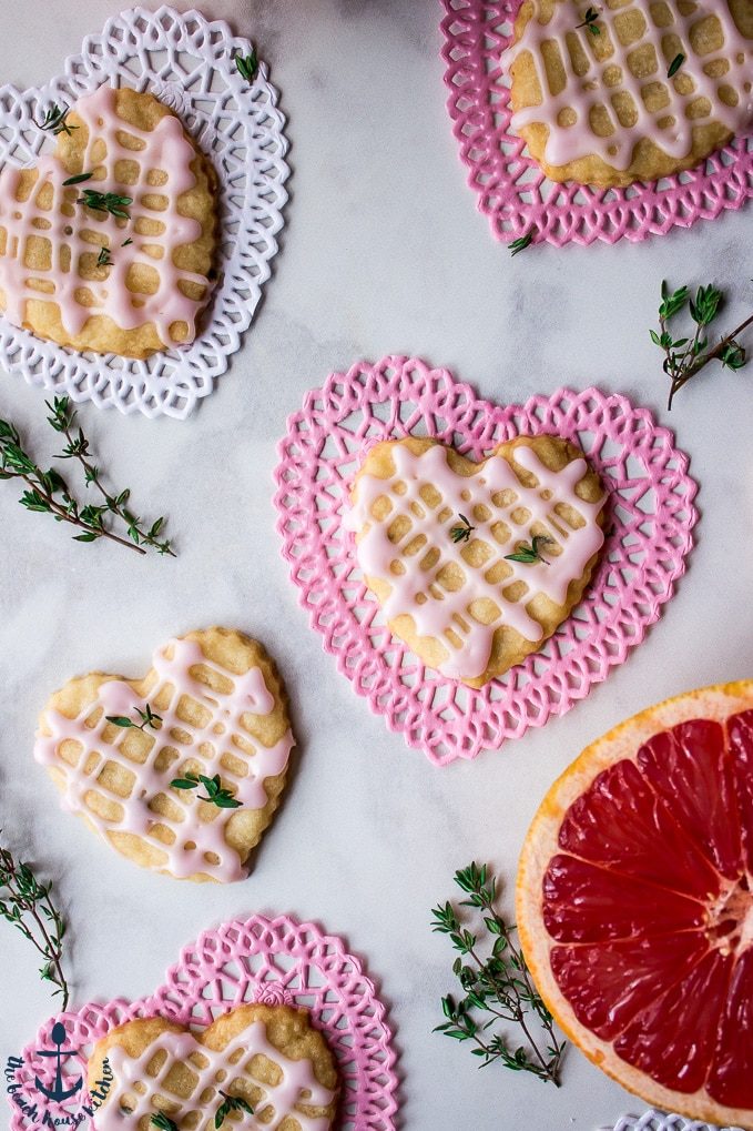 Overhead photo Pink Grapefruit and Thyme Shortbread Heart cookies on pink and white Valentine heart doilies with sprigs of thyme and pink grapefruit.