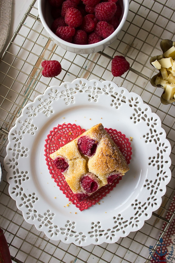 Overhead shot of one white chocolate raspberry bar on heart doily on white plate on wire rack with raspberries and chopped white chocolate in bowls.