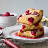 Stack of white chocolate raspberry bars on white plate on top of wire rack with raspberries in bowl in background.