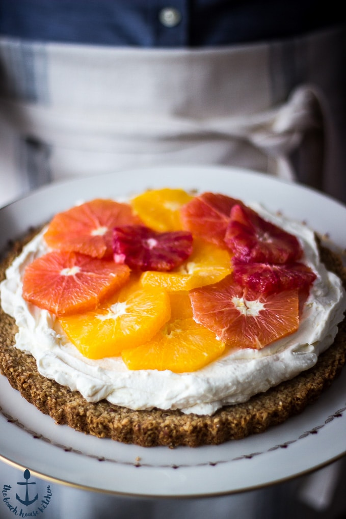 Person holding white plate with winter citrus mascarpone tart on it.