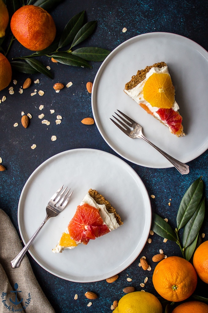 Overhead shot of two white plates with a slice of winter citrus mascarpone tart and fork on them. Oranges, lemons and nuts in background.