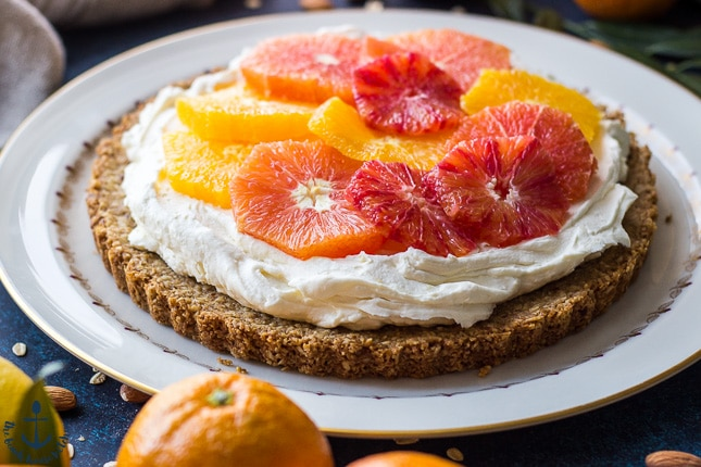 Winter citrus mascarpone tart on white plate with a few oranges around it.
