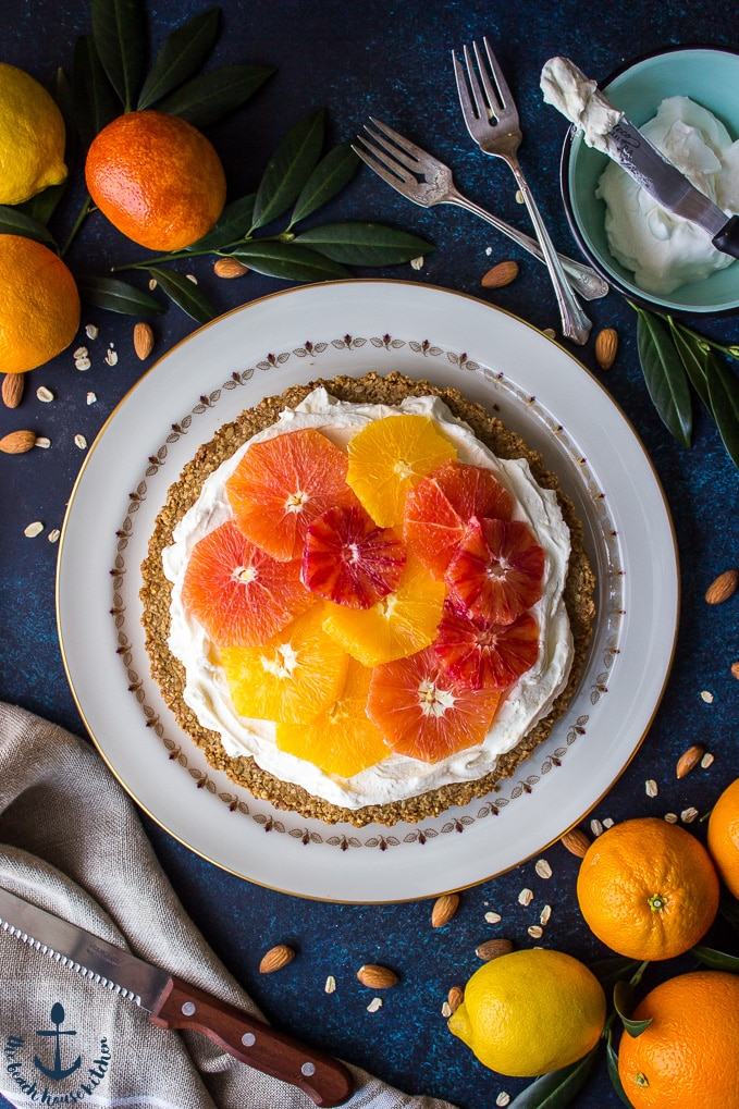 Overhead shot of winter citrus mascarpone tart on white plate crust with oranges, lemon, sharp knife, forks and bowl filled with whipped cream in background.