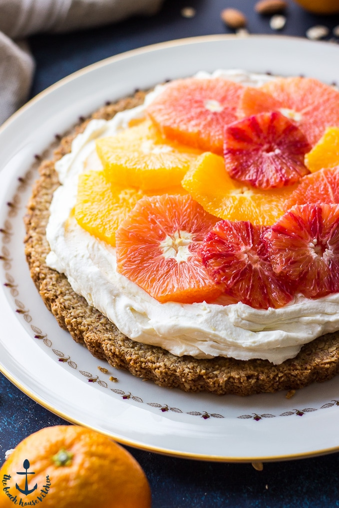 Winter citrus mascarpone tart on white plate with one orange in front of plate.