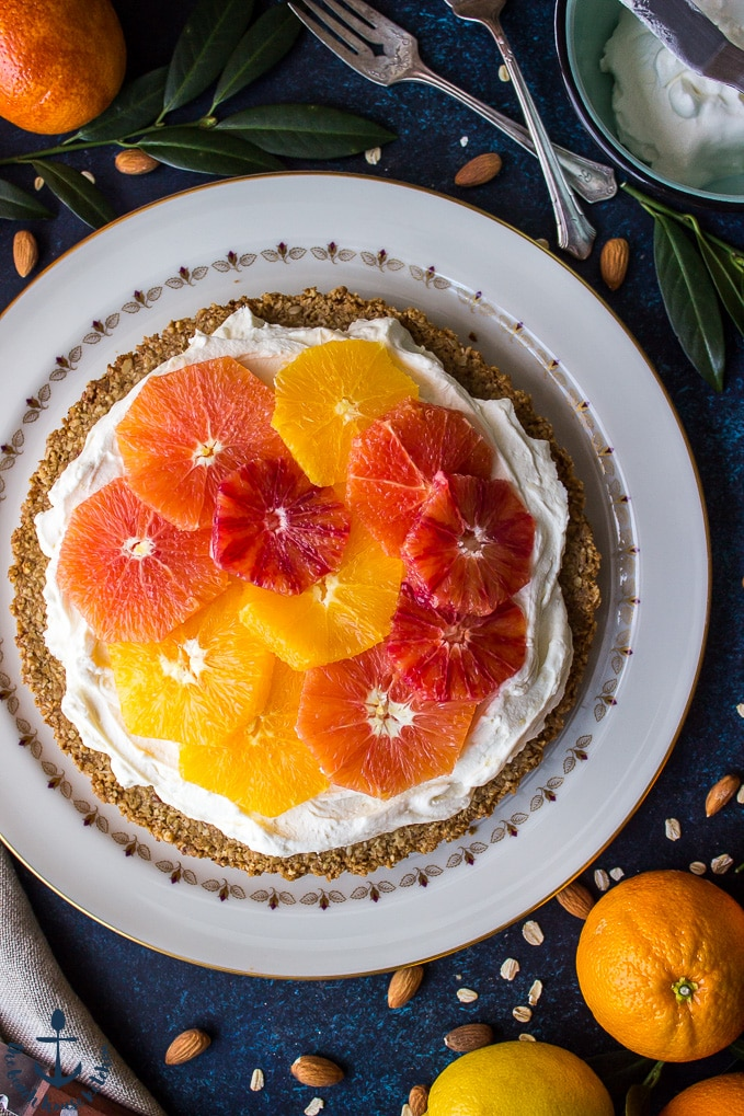 Overhead shot of winter citrus mascarpone tart on round white plate with oranges, lemon, forks and bowl filled with whipped cream in background