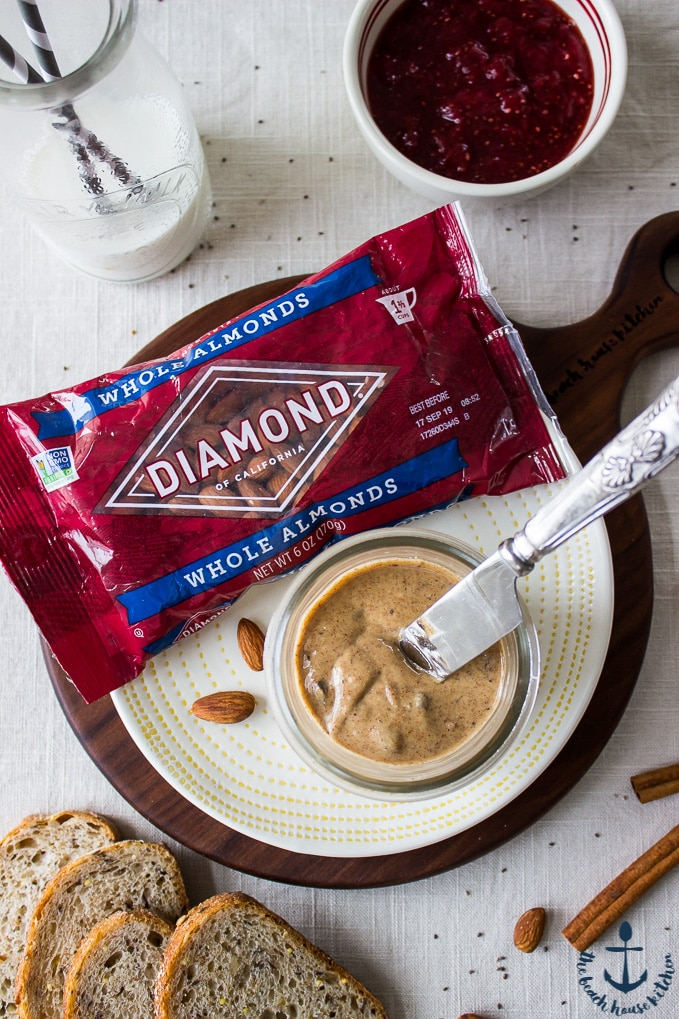 An overhead photo of a red bag of Diamond Whole Almonds with a jar of almond butter on a white plate.