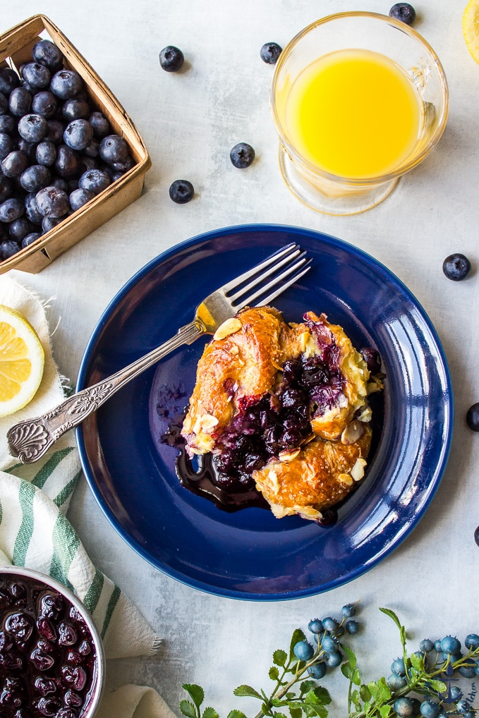 An overhead photo of a serving of Blueberry Croissant Bread Pudding with Blueberry Sauce on a blue plate with a silver fork with a glass of orange juice.