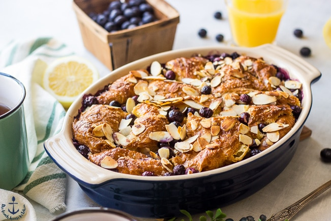 Blueberry Croissant Bread Pudding in a blue oval dish with a carton of blueberries and a glass of orange juice in the background.