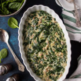 Overhead photo of Creamed Spinach in white oval dish on a blue background.