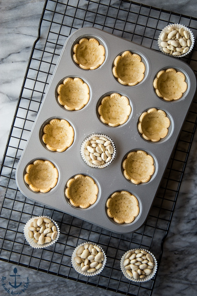 Overhead photo of mini muffin tin on a wire rack filled with pie shells