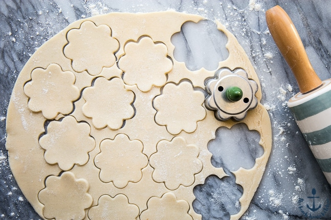 Overhead photo of rolled out dough with flower cutouts for Mini Lemon Meringue Pies