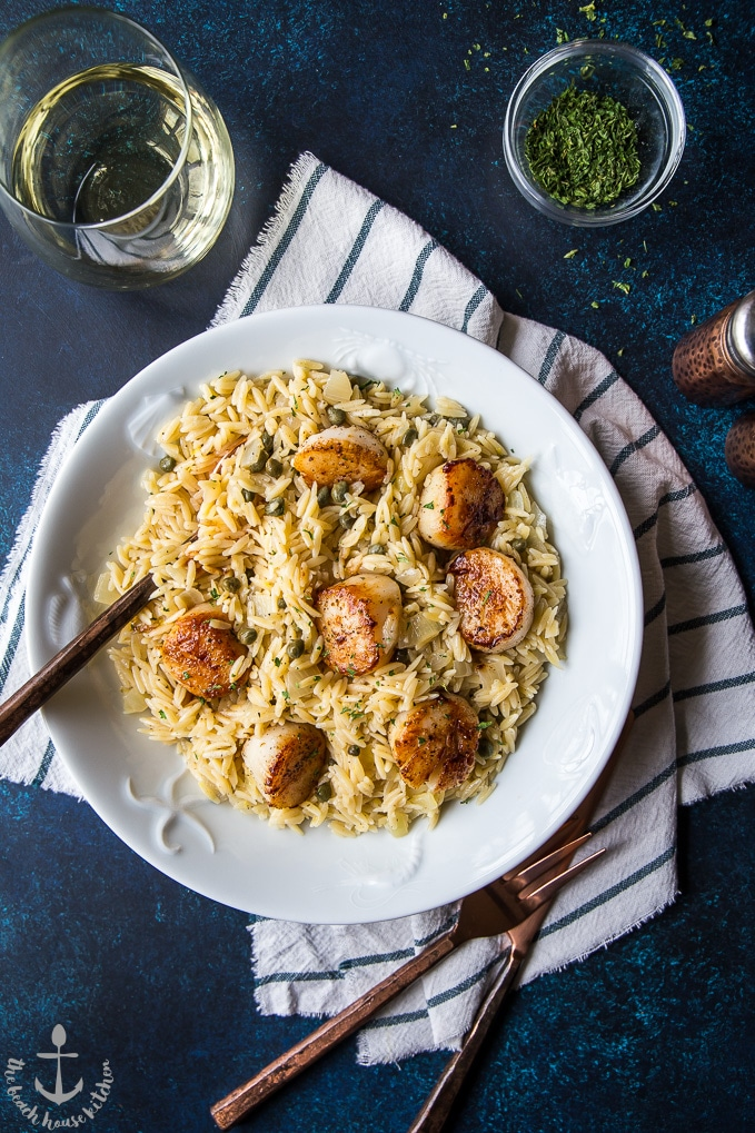 A big plate full of the delicious pan seared scallops with orzo piccata and a glass of wine right next to the plate