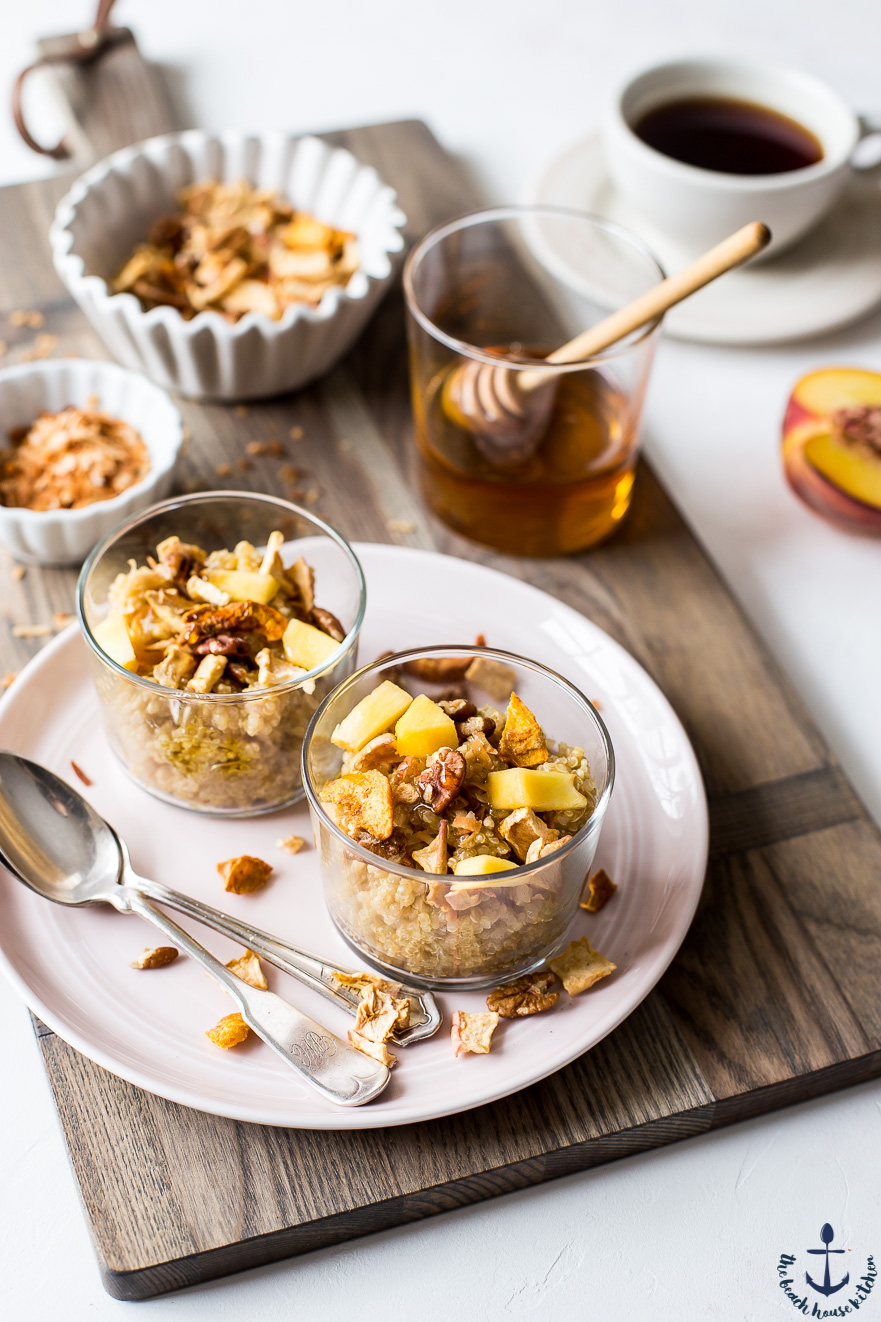 Two Peachy Quinoa breakfast bowls in glass cups on pink plate