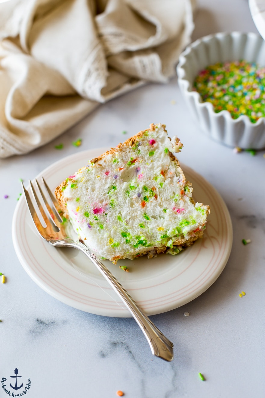 A slice of Funfetti Angel Food Cake on a plate with a fork