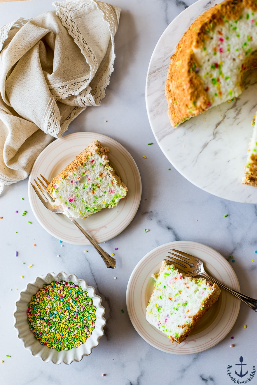 Funfetti Angel Food Cake slices on plates with a bowl of sprinkles