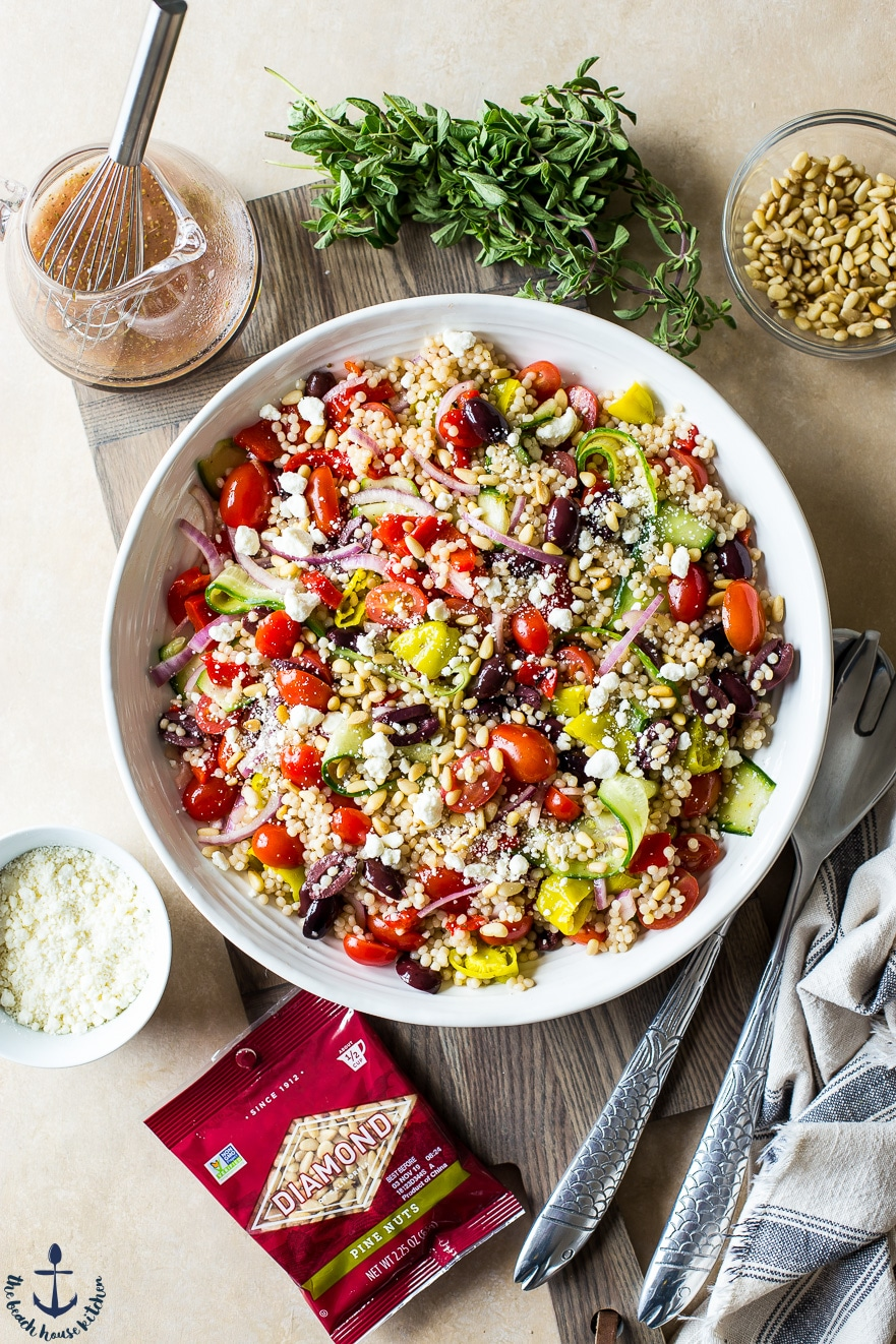 Overhead photo of Greek Couscous Salad on a wooden board