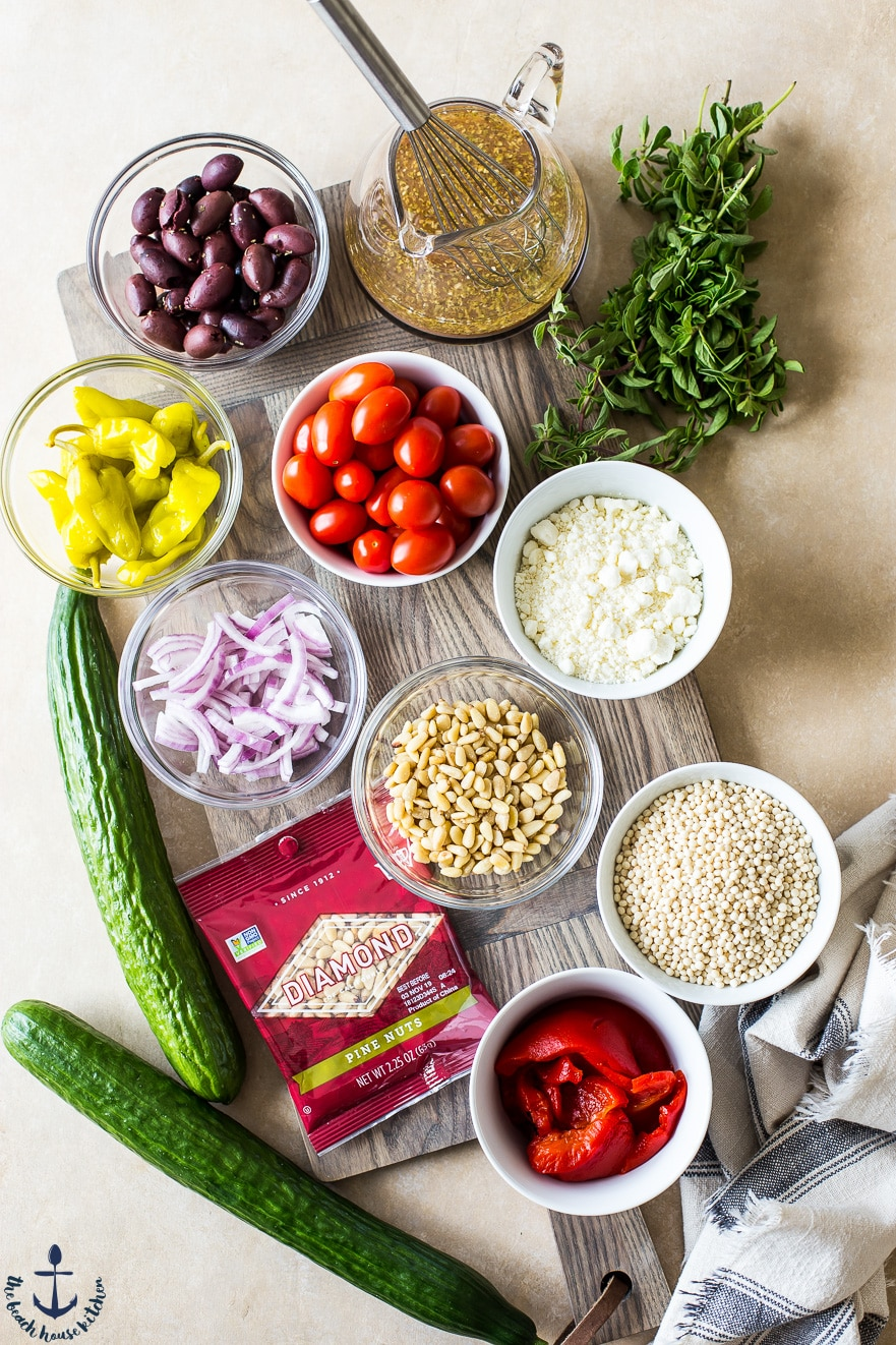 Ingredients in bowls for Greek Couscous Salad on a wooden board