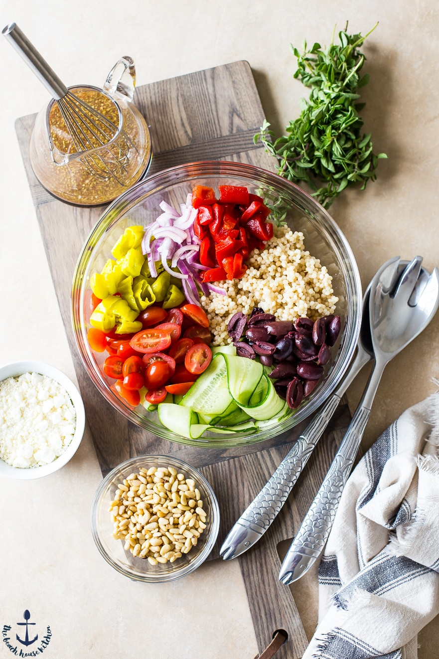 Ingredients for Greek couscous salad in a clear bowl on a wood board