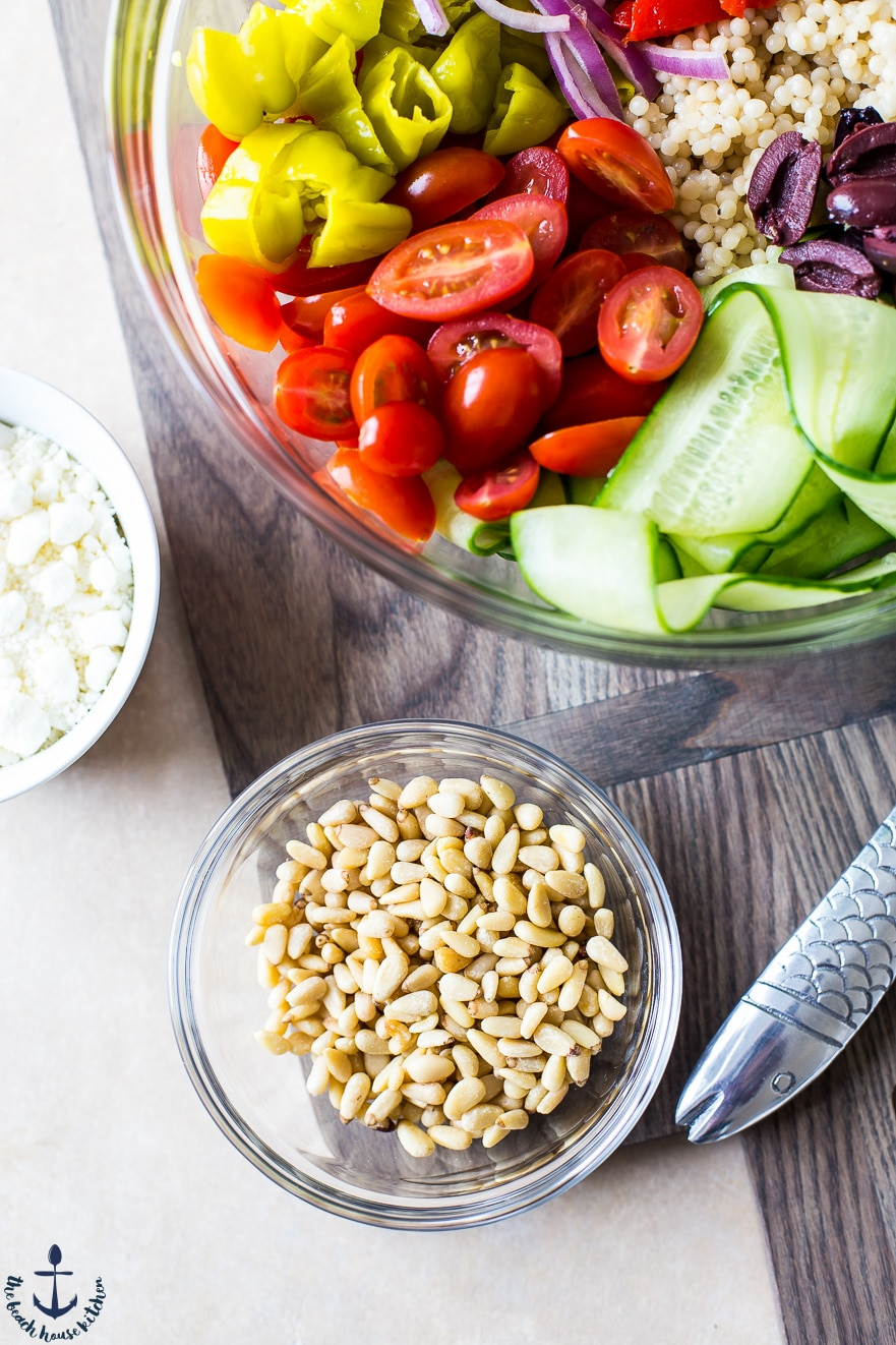 Overhead photo of pine nuts in a bowl and Greek couscous salad ingredients in a bowl.