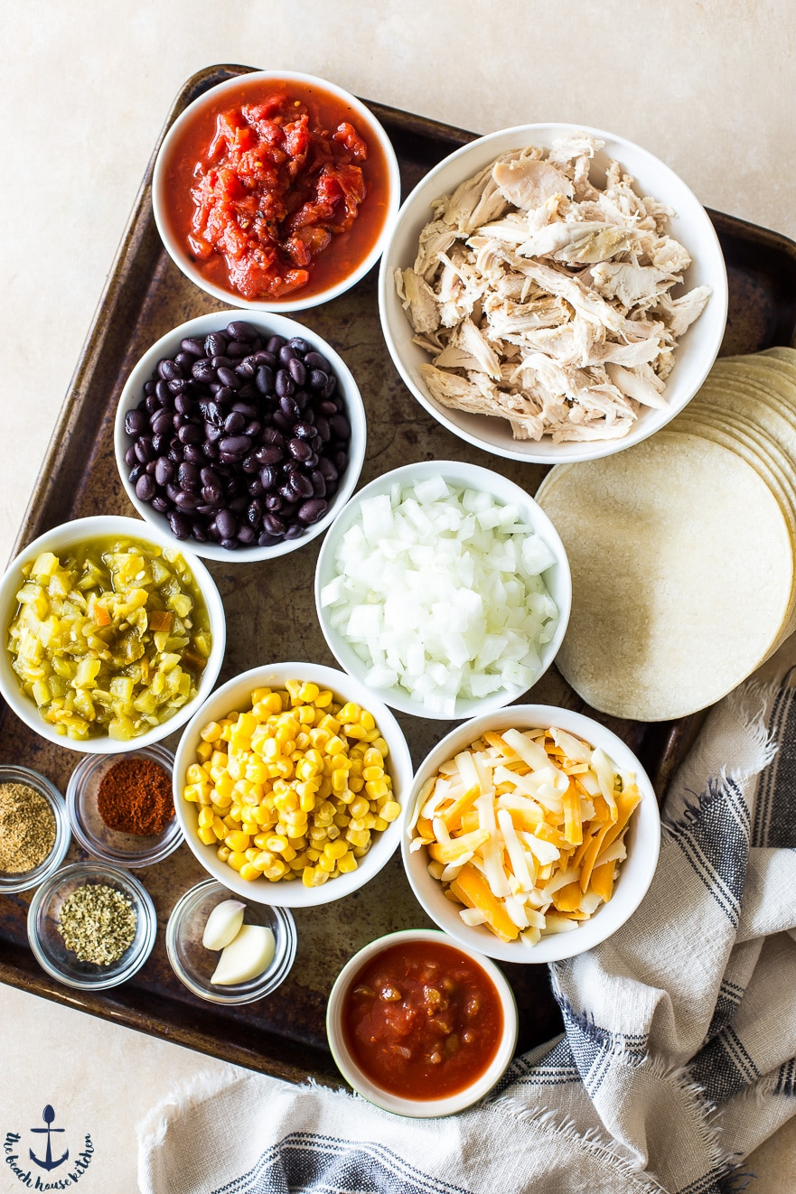 Overhead photo of ingredients for chicken, black bean and tortilla casserole in white bowls