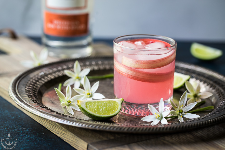 Photo of a pink spiced rhubarb collins cocktail on a silver tray surrounded by flowers and limes.