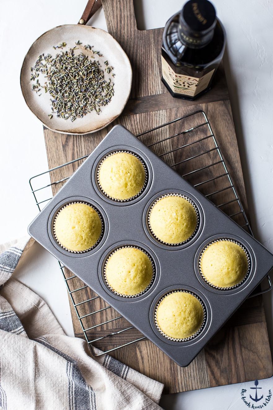 yellow cupcakes in cupcake pan on wooden board