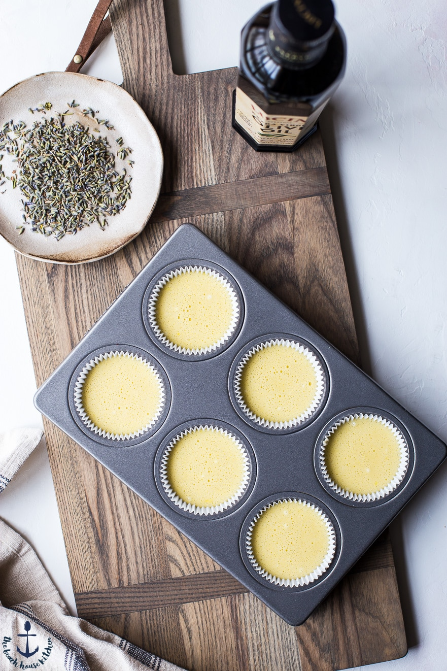 cupcake pan filled with cucpcake batter on wooden board