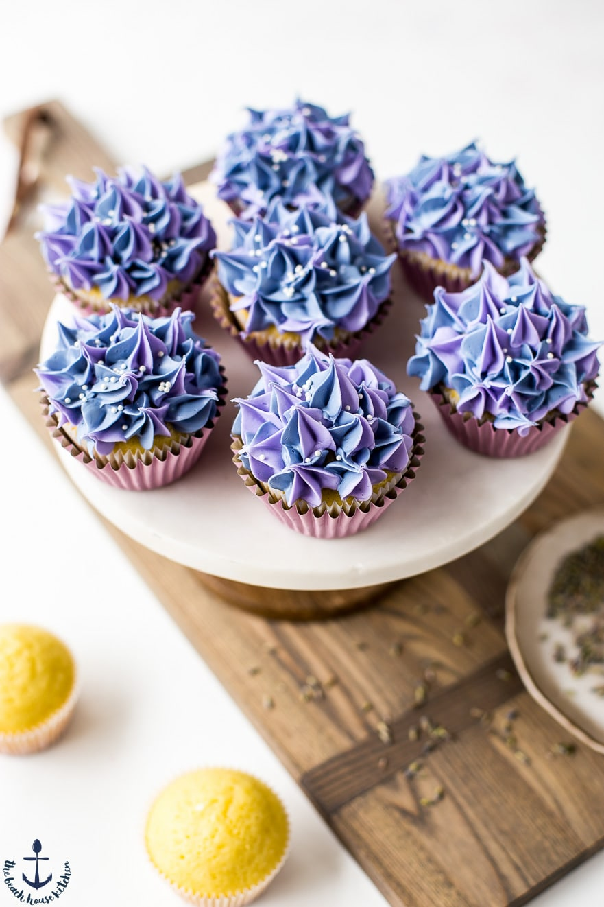 Lemon olive oil cupcakes with lavender buttercream on cakestand on wooden board