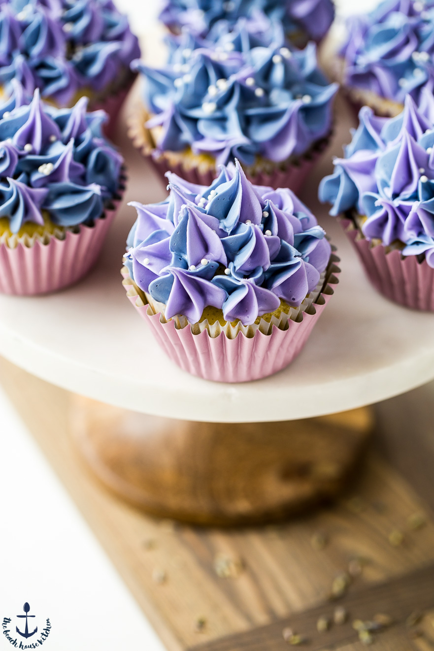Photo of lemon olive oil cupcakes with lavender buttercream on a cake plate with wooden stand