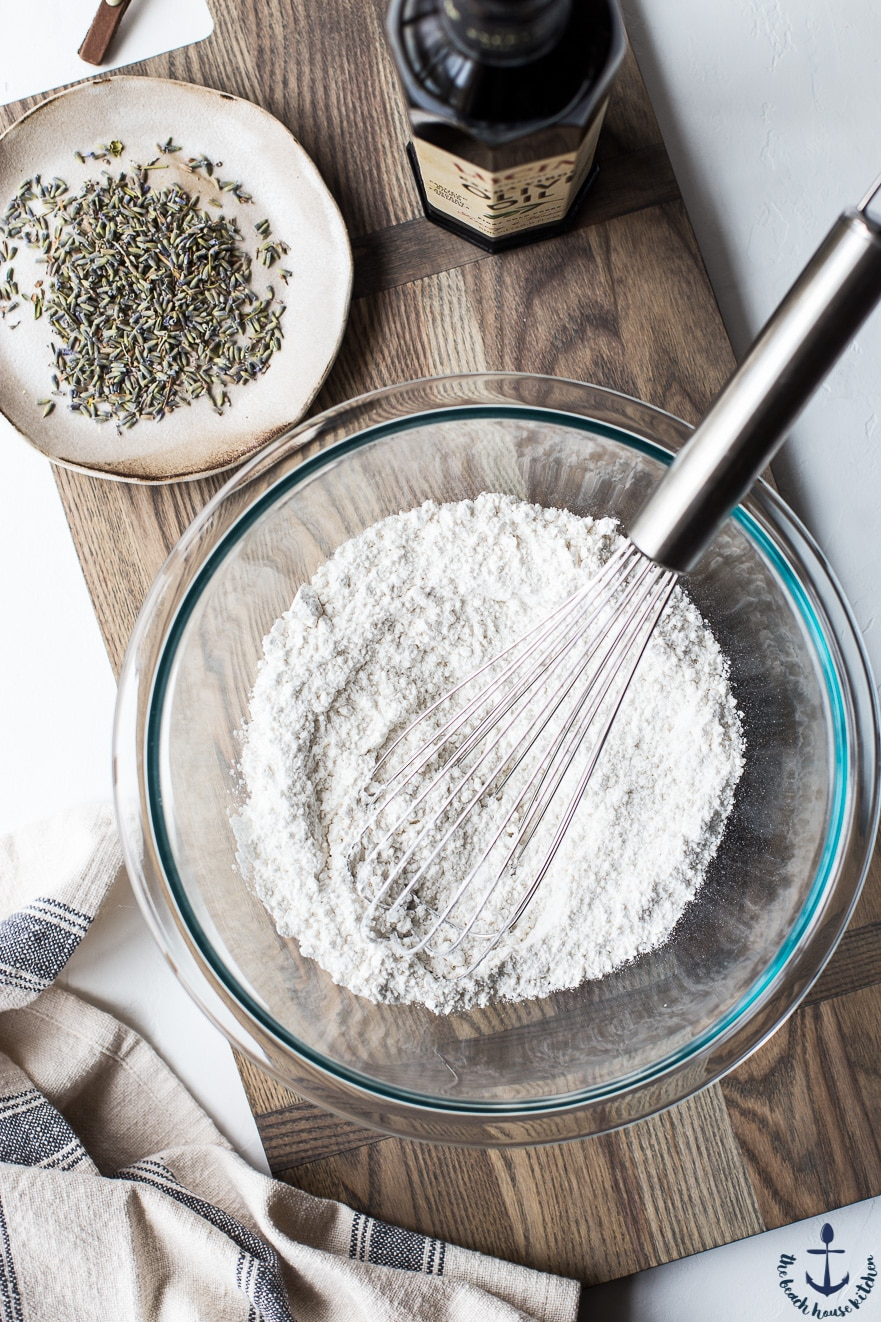 Flour in clear bowl with silver whisk on wooden board