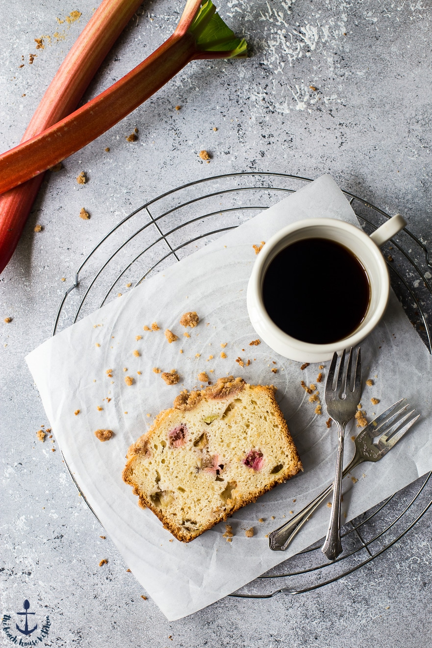 Overhead photo of slice of rhubarb crumb loaf, cup of coffee and forks