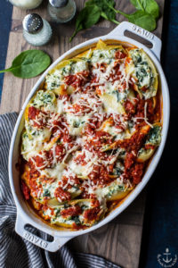 Overhead photo of easy spinach stuffed shells in a white dish on a wooden board