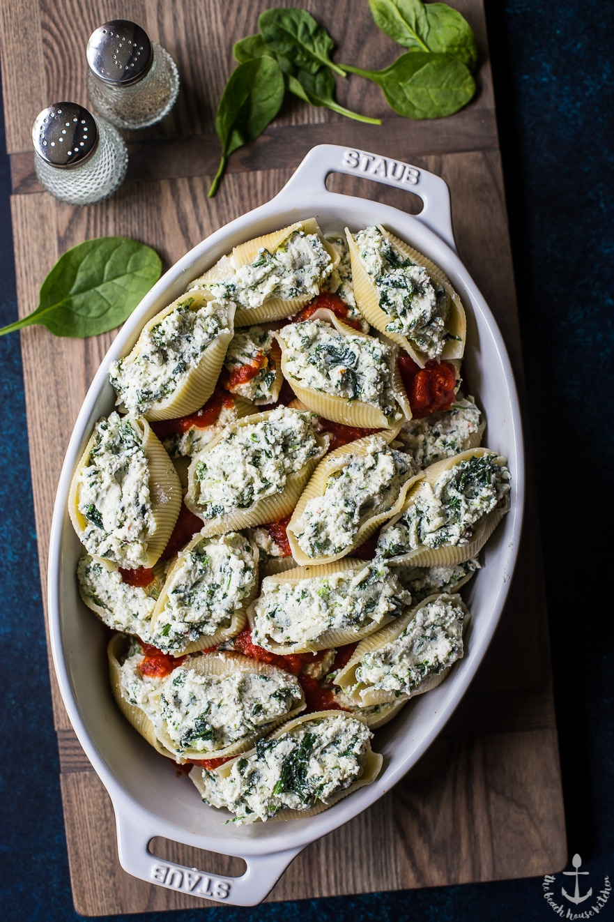 Precooked easy spinach stuffed shells in white dish on wooden board