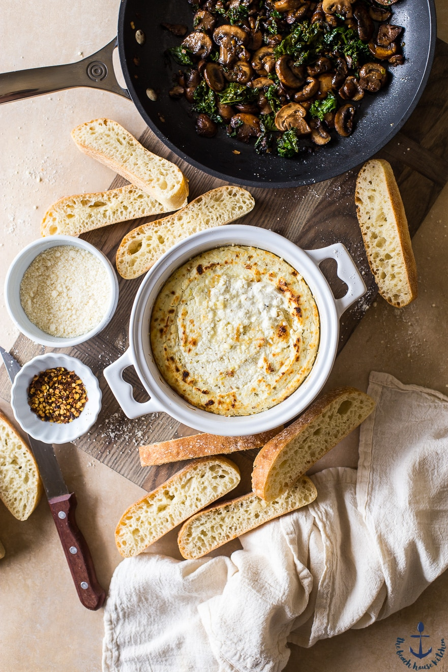 Overhead photo of baked ricotta in a white crock surrouned by bread slices