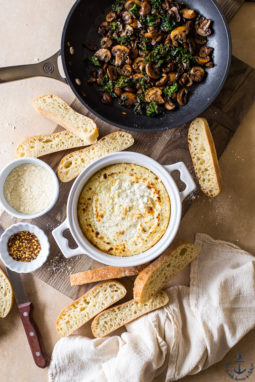 Overhead photo of baked ricotta in white crock with mushroom, shallot and kale topping