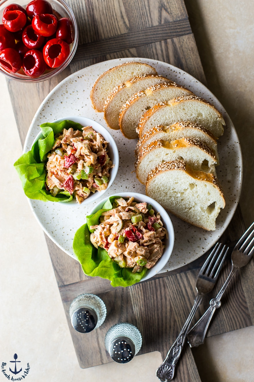 Overhead photo of Chicken salad with peppadew peppers and olives on a plate with bread slices