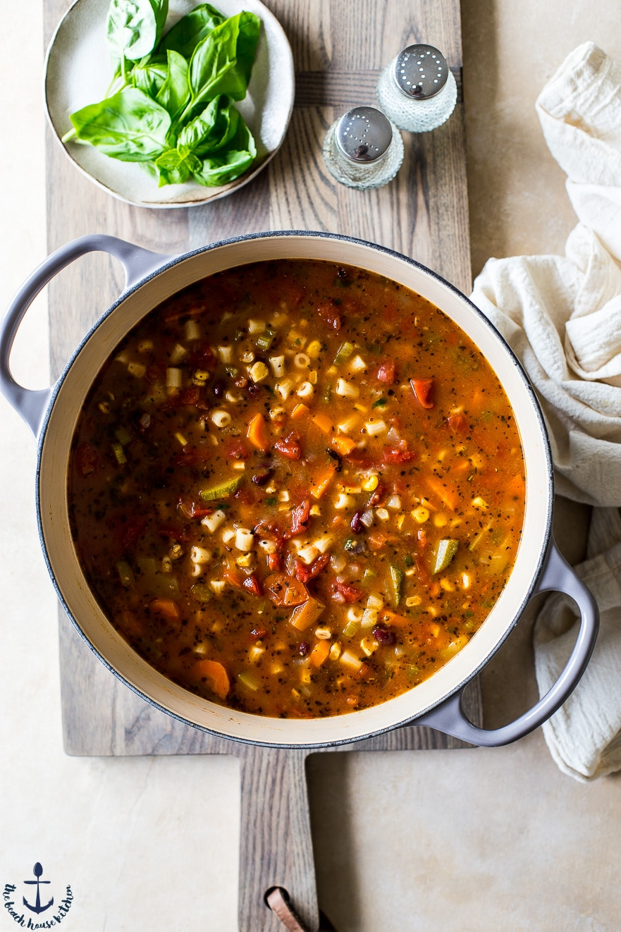 Overhead photo of summer minestrone soup in pot on wooden board