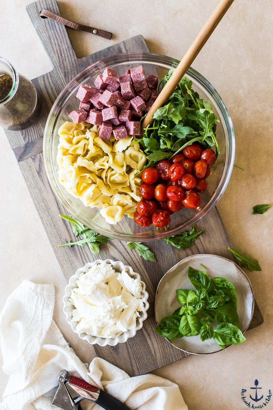 Overhead photo of ingredients for Tortellini, Roasted Tomato and Salami Salad in a clear bowl