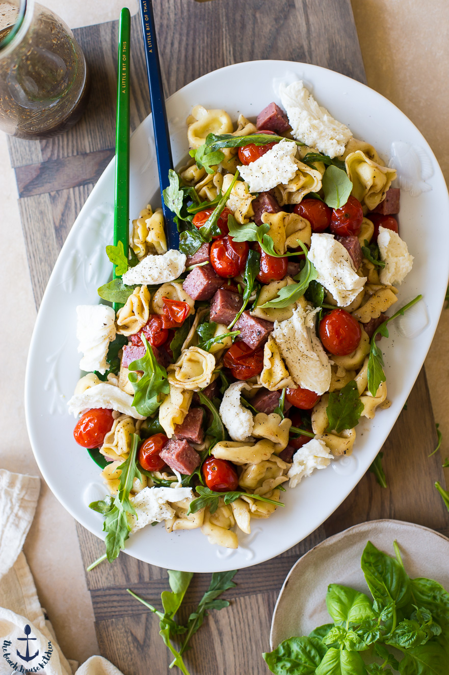 Overhead photo of Tortellini, Roasted Tomato and Salami Salad on a white plate